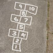 stock photo of hopscotch  - Kids game of hopscotch drawn on sidewalk in chalk - JPG