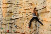 stock photo of climbing wall  - active young woman on rock wall in sport center - JPG
