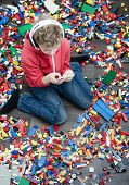 foto of toy phone  - Spoiled kid with to many toys playing on smartphone surrounded by toys - JPG