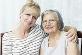 stock photo of only mature adults  - Beautiful mature daughter hugging her senior mother - JPG