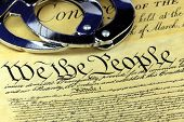 stock photo of bill-of-rights  - Handcuffs on US constitution with American flag  - JPG