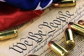 stock photo of bill-of-rights  - US Constitution Bill of Rights with 45 caliber bullets and American flag - JPG