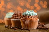 Tasty cupcakes with butter cream, on wooden table, on lights background