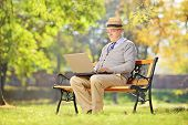 stock photo of work bench  - Senior man with hat sitting on a wooden bench and working on a laptop in a park - JPG