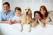 stock photo of labrador  - Portrait of happy family with their pet looking at camera - JPG