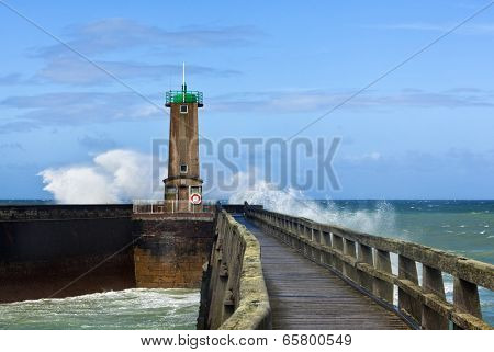 North Sea waves breaking at a lighthouse of the port entrance of Fecamp, Normandy