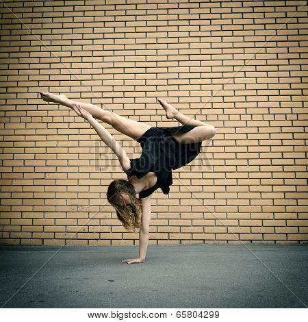 Attractive teen girl dancing outdoor against bricks wall. Toned.
