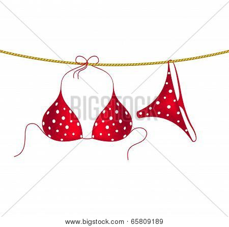 Red bikini suit with white dots hanging on rope