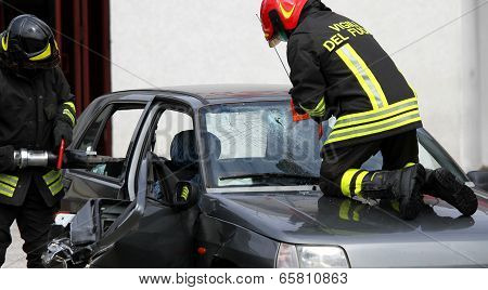 Firefighters In Action While They Open The Car After The Accident To The Driver Trapped