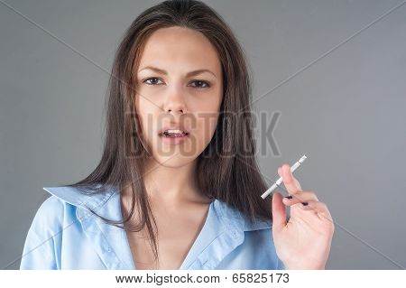 Attractive young brunette woman with cigarette