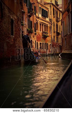 View of gondola with gondolier at narrow street of city. Venice