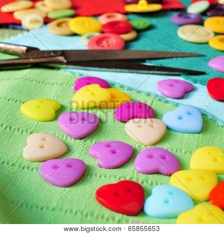 buttons of many colors and rusty scissors on some pieces of fabric of different colors
