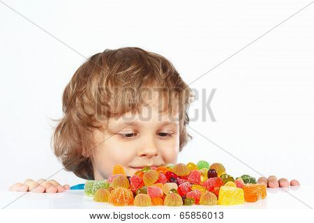 Little child with jelly candies on white background