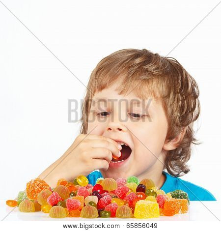 Little boy eating colored jelly candies on white background