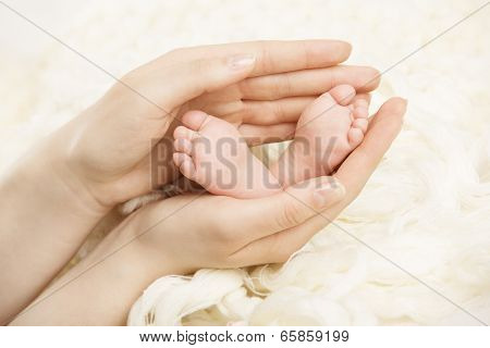 Newborn Baby Feet Mother Holding In Hands. New Born And Parent