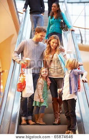 Family On Escalator In Shopping Mall Together