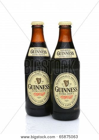 Two Guinness Extra Stout Bottles With Condensation