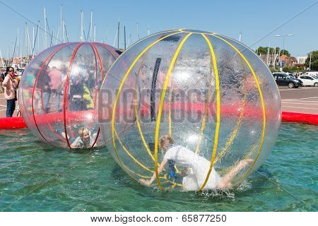 Children Have Fun Inside Plastic Balloons On The Water During A Fishing Fare