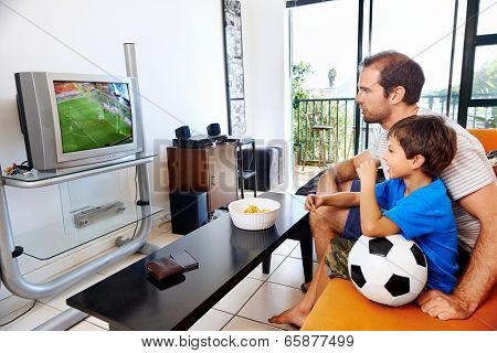 Father and son watching football world cup soccer on tv together in living room on sofa being excited fans