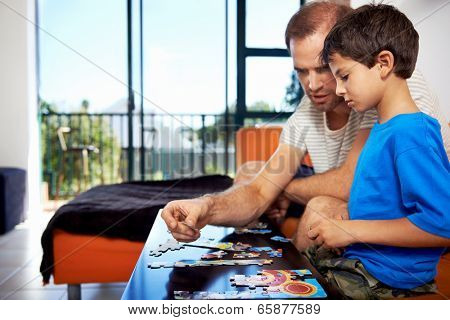 A dad and his son bonding over piecing a puzzle together