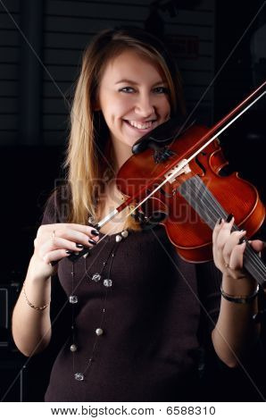 Young Female Play On Violin In Music Study