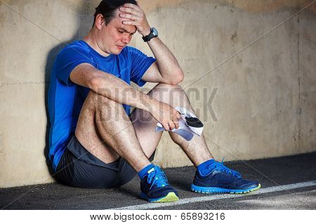 Upset Young Male Runner Resting Leaning Against Wall.