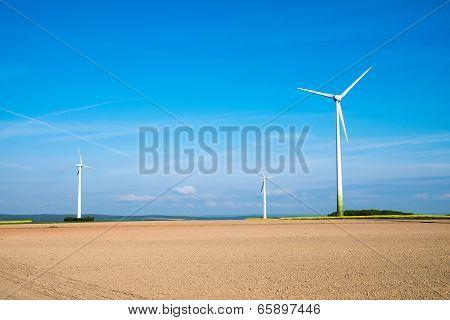 Windwheels behind a barren field