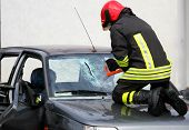 image of firehouse  - Fireman with protective overalls and work gloves while breaking a car windshield - JPG