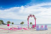 stock photo of wedding arch  - wedding arch decorated with flowers on tropical sand beach - JPG