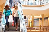 picture of escalator  - Two Female Friends On Escalator In Shopping Mall - JPG