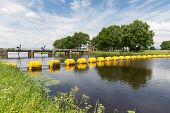 picture of barricade  - Barrage in Dutch river Vecht with a floating yellow barricade - JPG