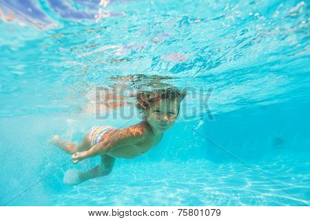 Looking boy moving while swimming undewater