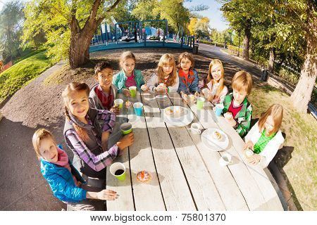 Wide angle lens view of children drinking tea