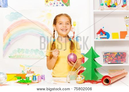 Cute small girl with brush painting New Year ball