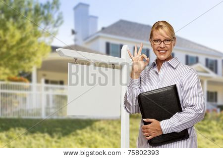 Attractive Female Real Estate Agent in Front of Blank Real Estate Sign and House.