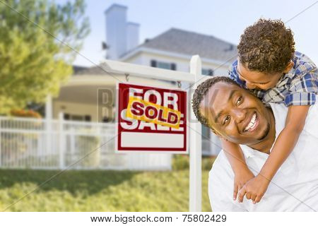 Happy African American Father and Mixed Race Son In Front of Sold Home For Sale Real Estate Sign and New House.