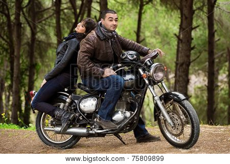 Bikers couple resting in the forest, two models posing on the motorcycle, active lifestyle, fashion style, romance and extreme concept