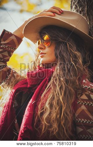 young woman wearing hat, sunglasses, red scarf and jacket, outdoor autumn fashion portrait in sunny park