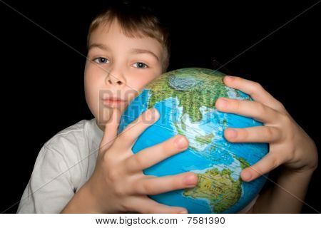 Boy Embracing Globe Of World Isolated On Black Background