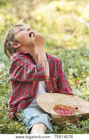 Teenage Boy Eating Red Wildberries In Forest