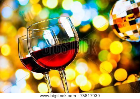 Two Red Wine Glasses Against Colorful Bokeh Lights And Sparkling Disco Ball Background