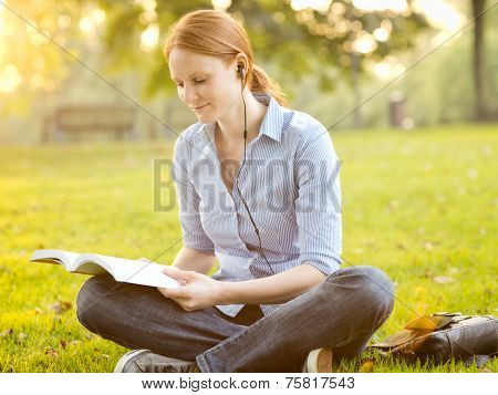 Student Reading A Book And Listening To Music