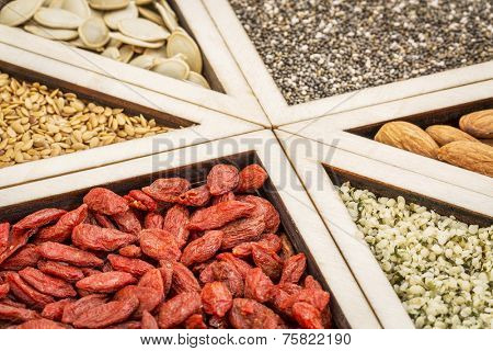 superfood abstract - dried goji berries, golden flax, pumpkin seeds, almonds, chia seeds and hemp seed hearts on a wooden tray
