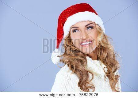 Pretty blond woman in a red Santa Hat with a merry smile looking over her shoulder to blank copyspace on blue for your Christmas greeting