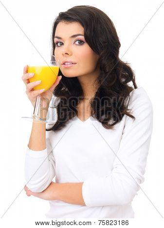 Healthy young woman sipping fresh orange juice from an elegant stemmed glass while looking sideways at the camera   over white