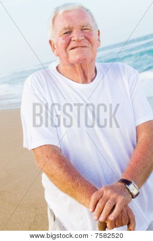 happy senior man on beach with cane