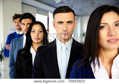 Group of a serious business people standing in a row in office