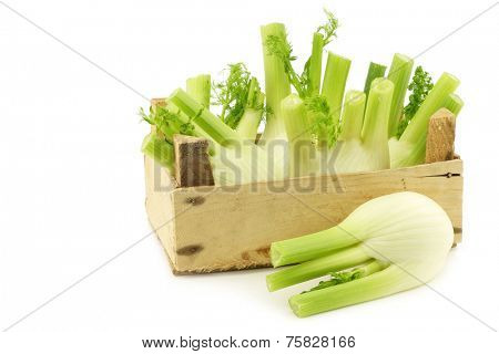 fresh fennel in a wooden crate on a white background