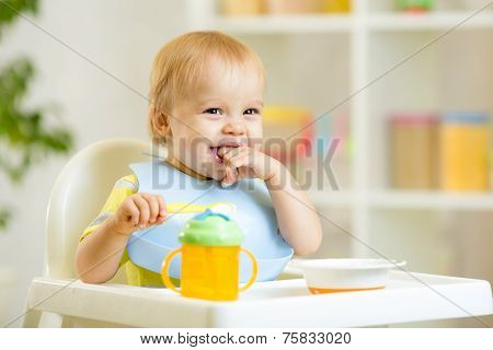 happy baby kid boy eating itself with spoon
