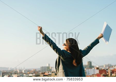 Business Woman Celebrating Success Towards City Skyline